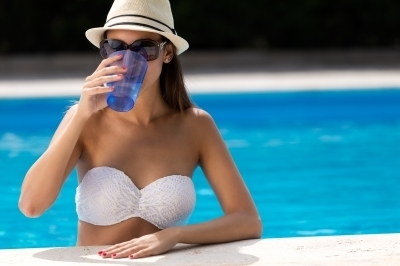 0325-beautiful_girl_drinking_water_at_the_swimming_pool.jpg